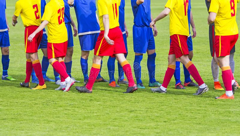 Handskakning för lag för fotboll två på fält arkivfoto