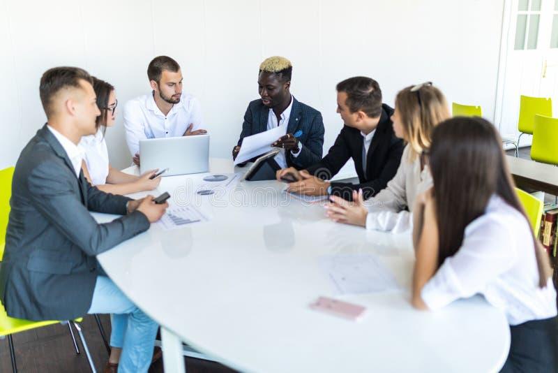 Handskakning i möte, dokument och grafer för mångfaldaffärslag på skrivbordet Projektmöte royaltyfri bild