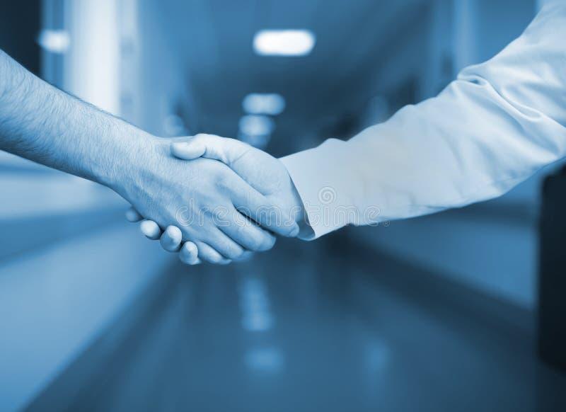 Handskakning i sjukhuskorridoren royaltyfria bilder