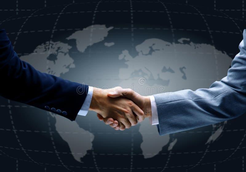 Handskakning med översikten av världen i bakgrund royaltyfri foto