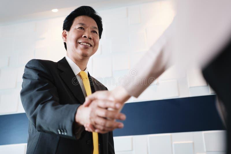 Handskakning mellan den lyckliga asiatiska chefen And Hispanic Businesswoman i regeringsställning arkivfoton