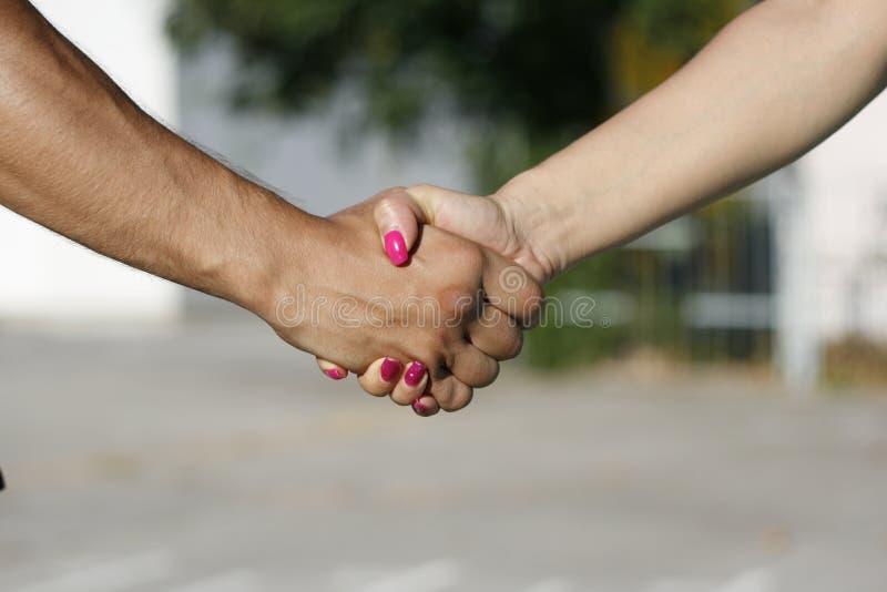 Handskakning mellan flickan och pojke, man och kvinna royaltyfria bilder