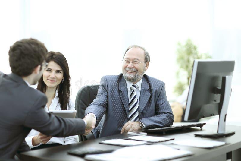 Handskakning mellan kollegor i arbetsplatsen i kontoret royaltyfri foto