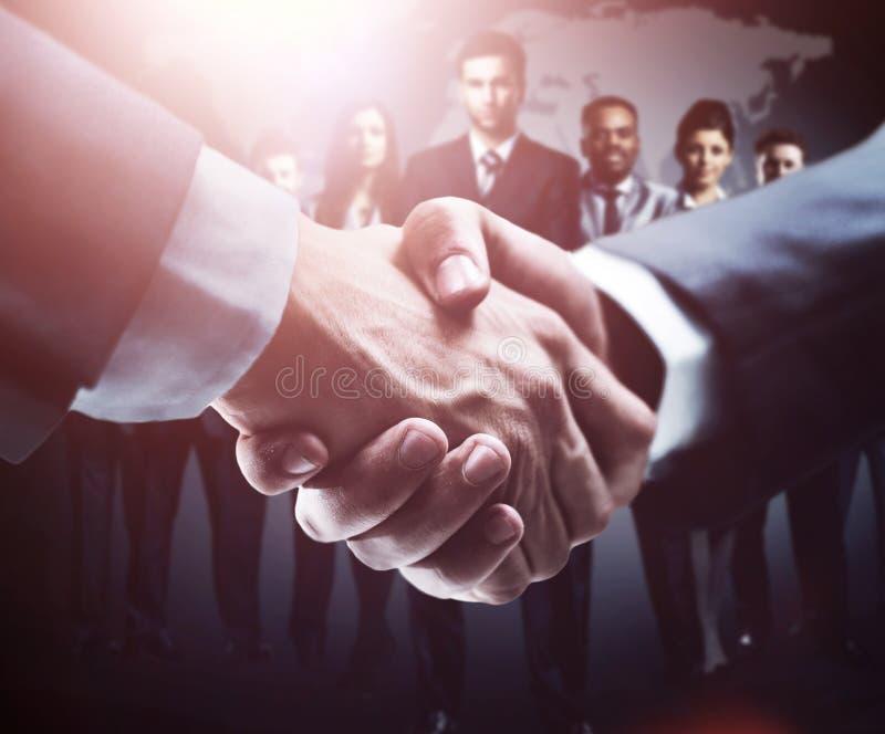 Handskakning på bakgrundsgruppen av affärsfolk i mörka färger royaltyfria bilder