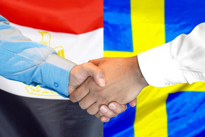 Handskakning på Egypten och Sverige flaggabakgrund royaltyfri foto
