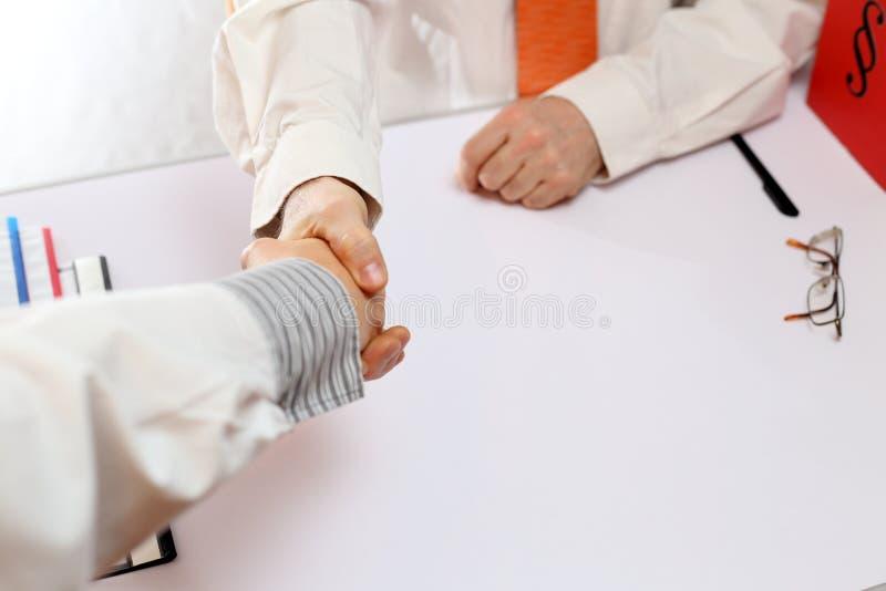 Handskakning på kontorsskrivbordet royaltyfri bild