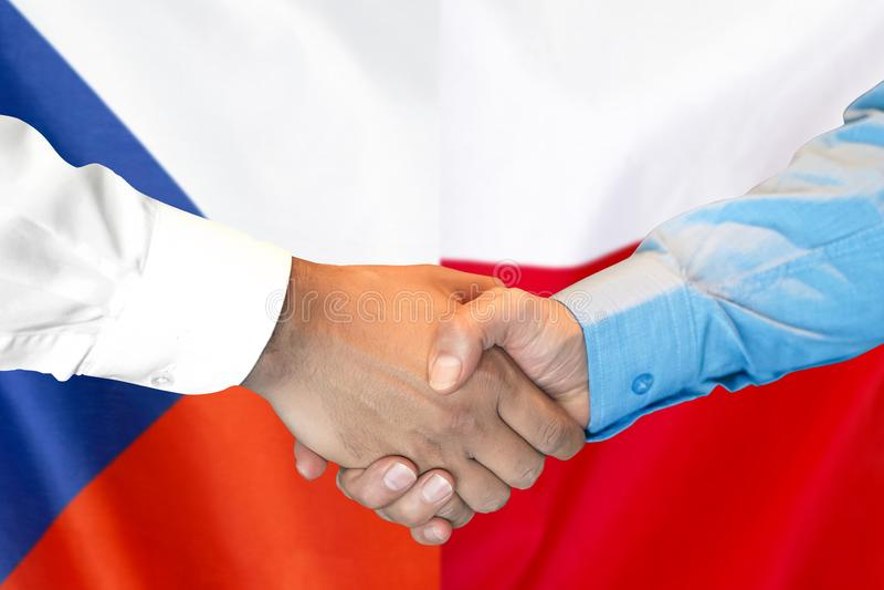 Handskakning på Tjeckien- och Polen flaggabakgrund arkivfoton