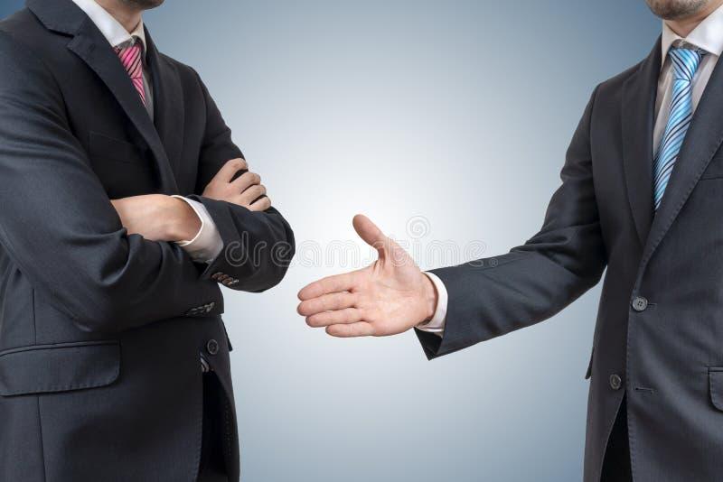 Handskakningavskräden Mannen vägrar skakahanden med affärsmannen som erbjuder hans hand arkivfoton