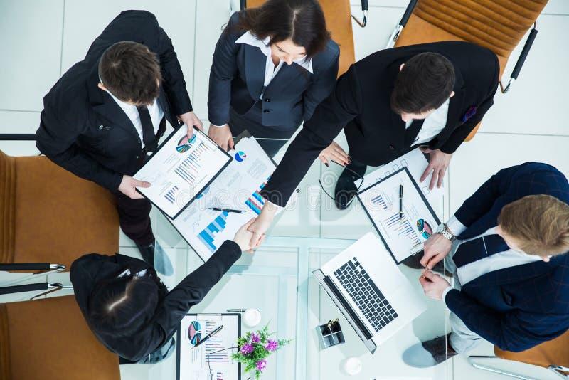 handskakningchef och finansdirektör efter godkännande av det finansiella planet av företaget i arbetsplatsen royaltyfri fotografi