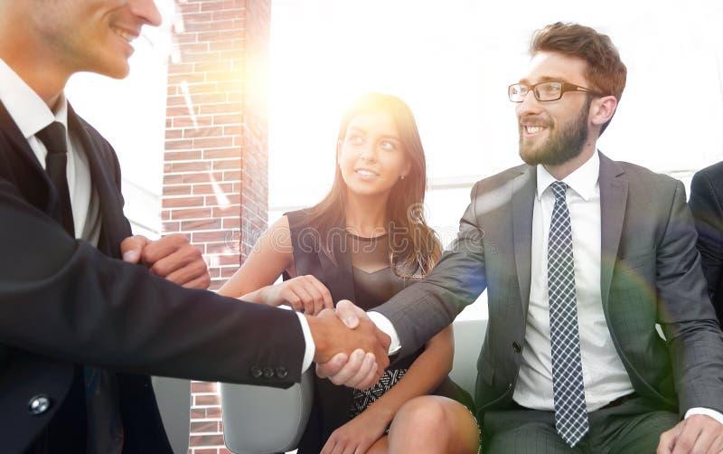Handskakningchef och klienten på ett möte i kontorslobben arkivfoton
