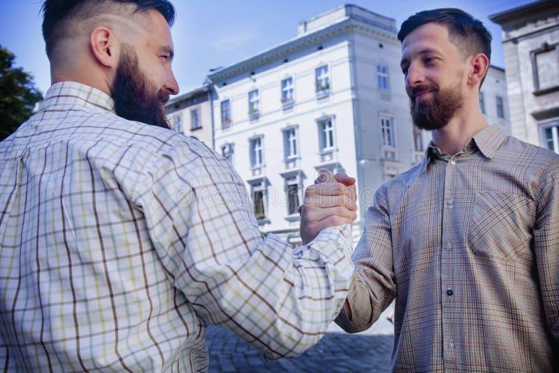 Handskakningen av två uppsökte hipstervänner som symbol av manlig stron fotografering för bildbyråer