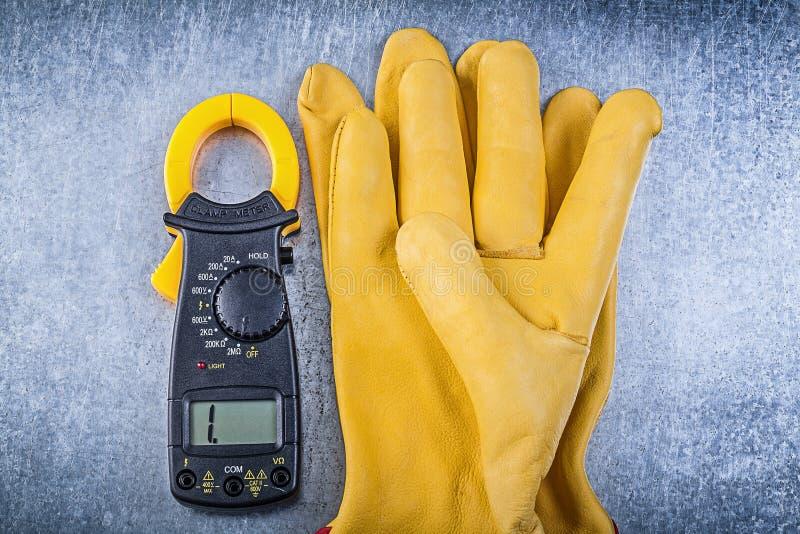 Handskar för Digital amperemetersäkerhet på metallisk bakgrund royaltyfri foto
