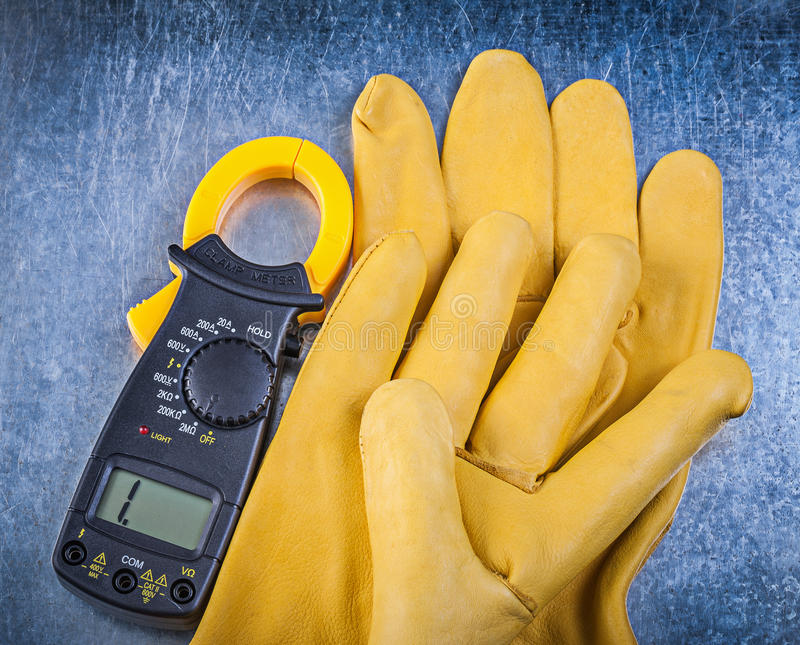 Handskar för Digital amperemetersäkerhet på metallisk bakgrund arkivbilder