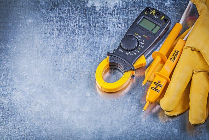 Handskar för elektrisk tester för Digital amperemeter skyddande på metallisk su royaltyfri fotografi
