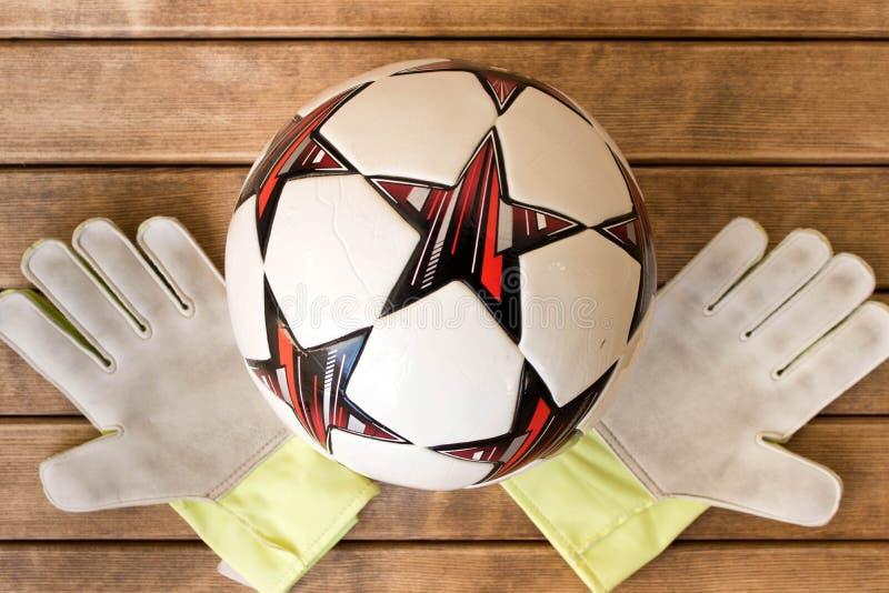 Handskar för fotbollboll och goaliepå träbakgrund arkivfoto