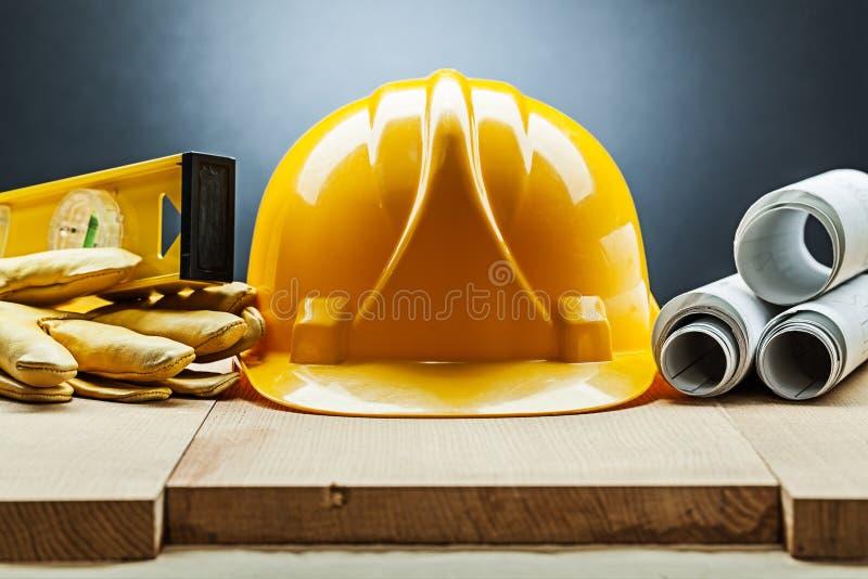 Handskar för gul hjälm för konstruktionssammansättning rullade jämna ritningar på trä royaltyfria bilder