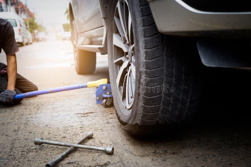 Handskar för mekaniker för ung man som bärande lyfter bilen på stålar för bilreparation i utomhus- ändrande plant gummihjul med s royaltyfria bilder