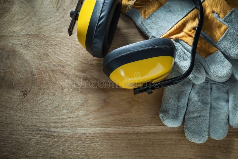 Handskar för säkerhet för öronskydd för oväsenförminskning på träbräde royaltyfria foton