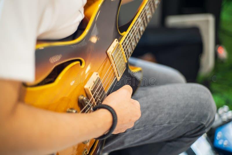 Handskar och gitarrer av unga gitarrer som spelar gitarrer arkivfoto