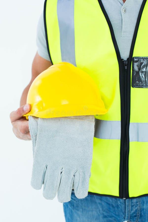 Handskar och hardhat för byggnadsarbetare hållande royaltyfria foton