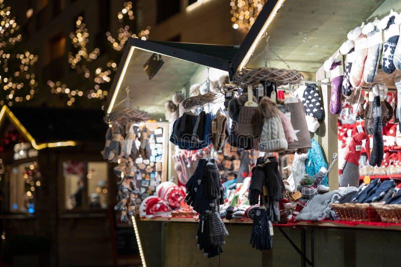 Handskar och hattar på jul marknadsför båset i meranoen södra tyrol under natt royaltyfria foton