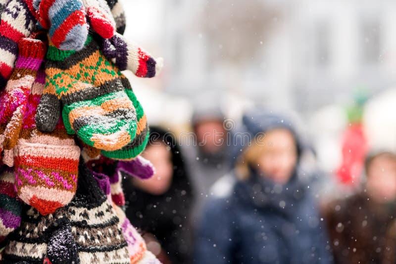 Handskar på skärm på en snöig dag i stad övervintrar biljettpris Jul arkivbild