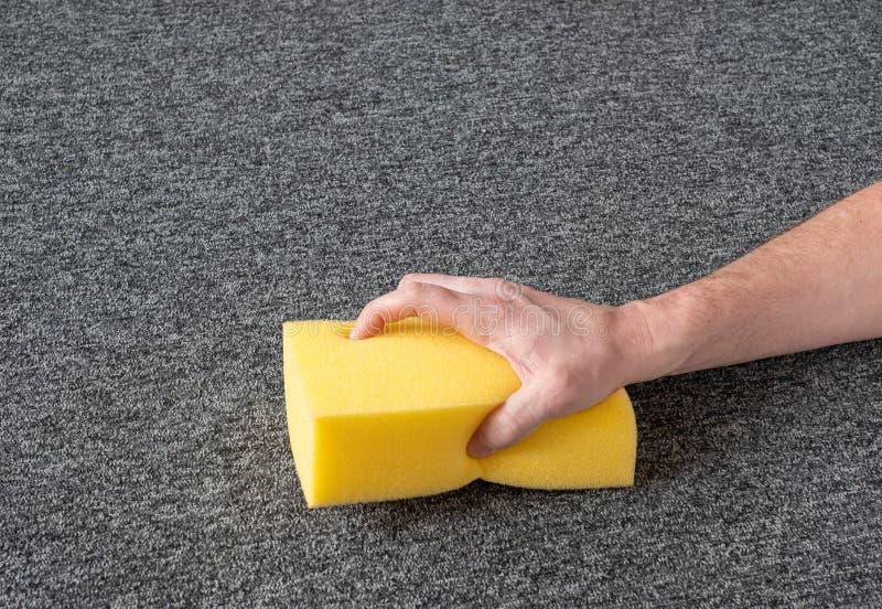 Handskar utan handskar, grå mattan med gul svamp kemtvätt royaltyfri fotografi