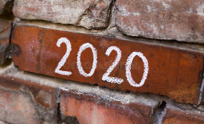 Handskrifttext 2020 på den gamla röda stadstegelstenväggen royaltyfri bild
