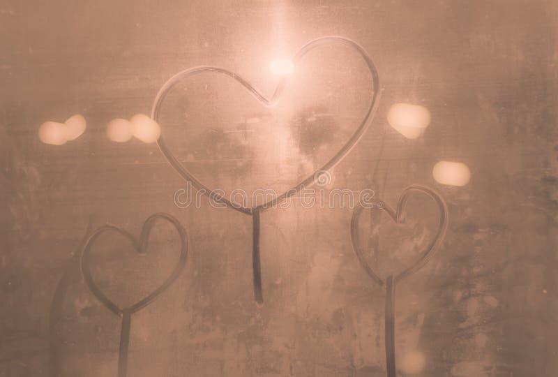 Handskriven hjärta på ett ångande exponeringsglas bokeh som är härlig eller som är söt i valentindagen för bakgrund royaltyfri foto
