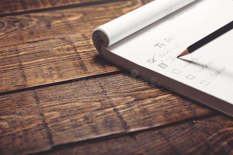 Handskriven lista av angelägenheter i en anteckningsbok på en träbakgrund, närbild royaltyfri fotografi