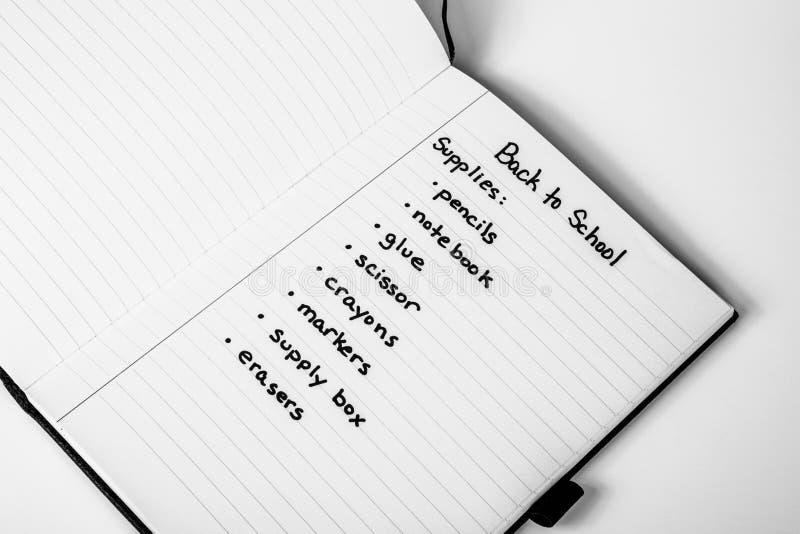 Handskriven shoppinglista av tillbaka till skolatillförsel arkivbild