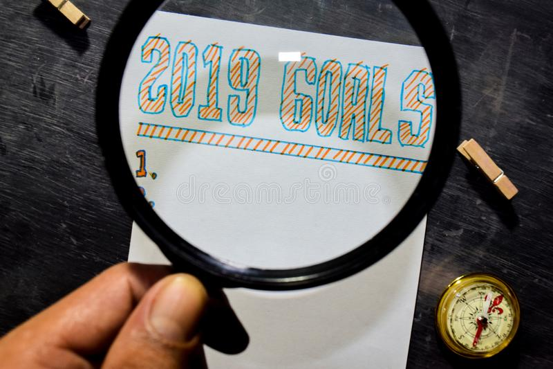 Handskriven text för 2019 mål på papperet med markören, kompasset och bruksförstoringsglaset fotografering för bildbyråer