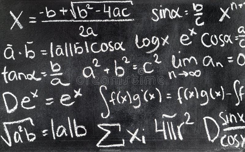 Handskrivna matematiska formler på den skriftliga svart tavla royaltyfria bilder