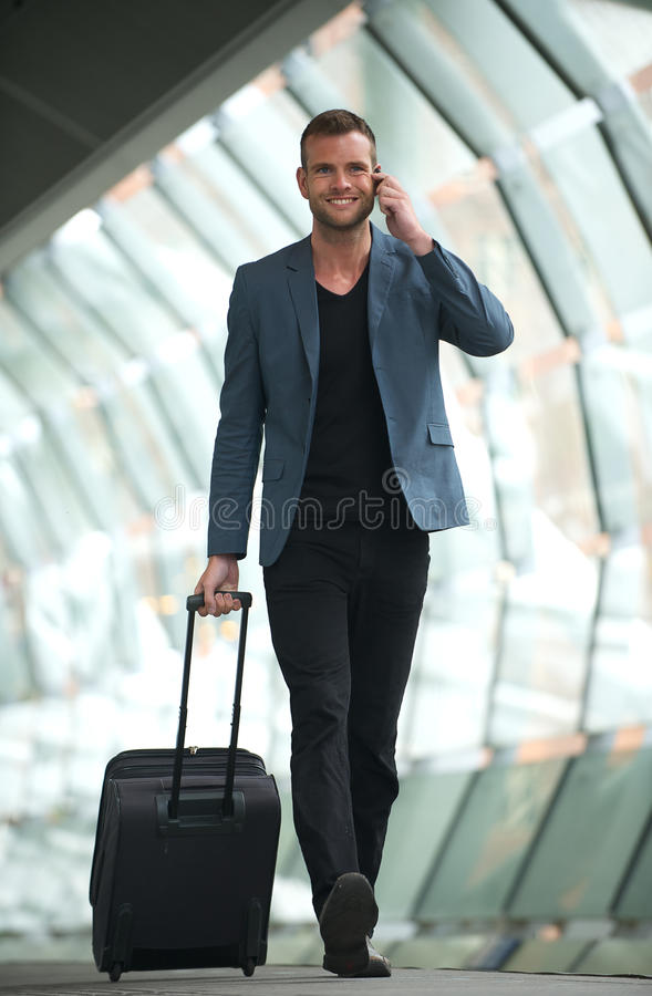 Handsom Man Walking In City With Cell And Suitcase Royalty Free Stock Image