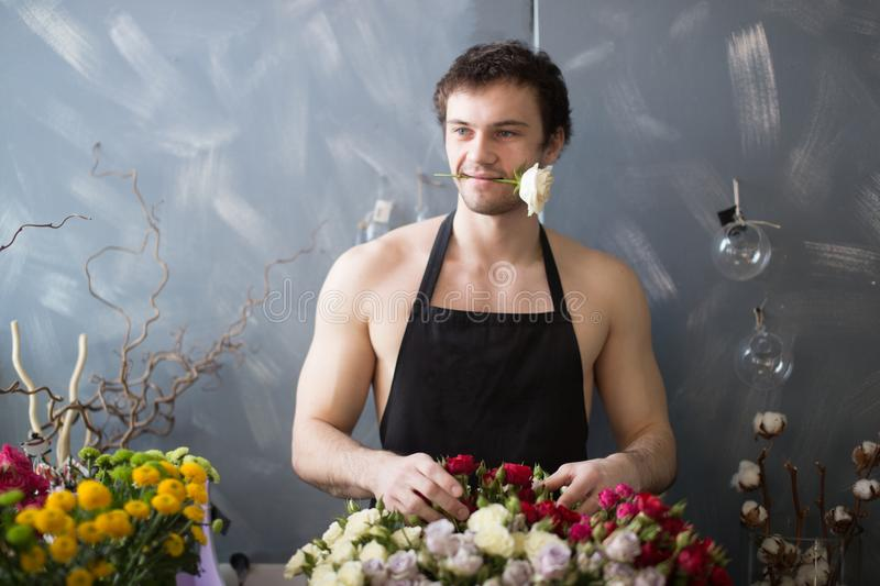 Handsom seller with rose standing behind bouquets. Thoughtful look stock photo