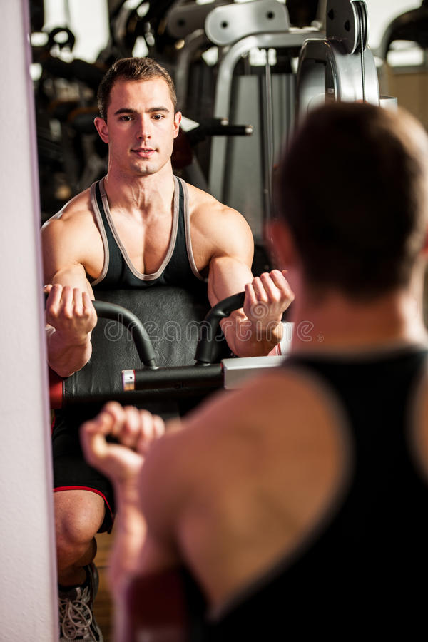 Handsom young man workout in fitness gym. For competition stock photography