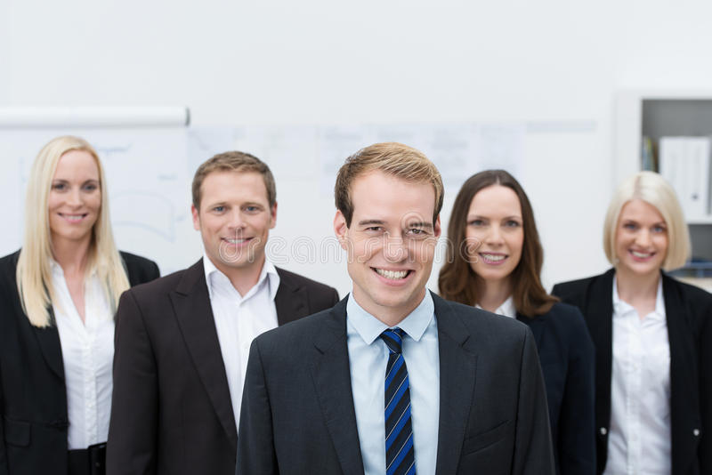 Handsom Young Manager With A Happy Team Behind Him Stock Photography