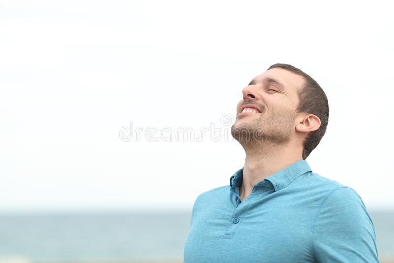 Handsome adult man breathing fresh air on the beach royalty free stock images