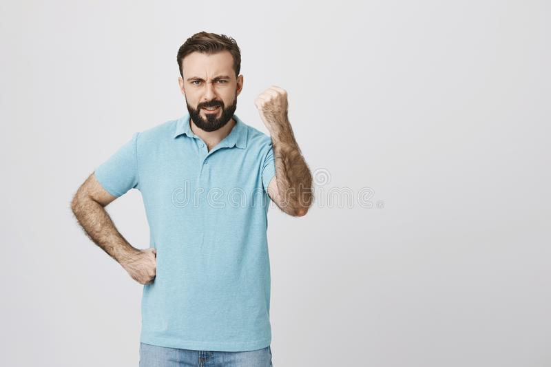 Handsome adult european man, wearing blue t-shirt and jeans showing fist with angry expression and hand on waist, while royalty free stock photography
