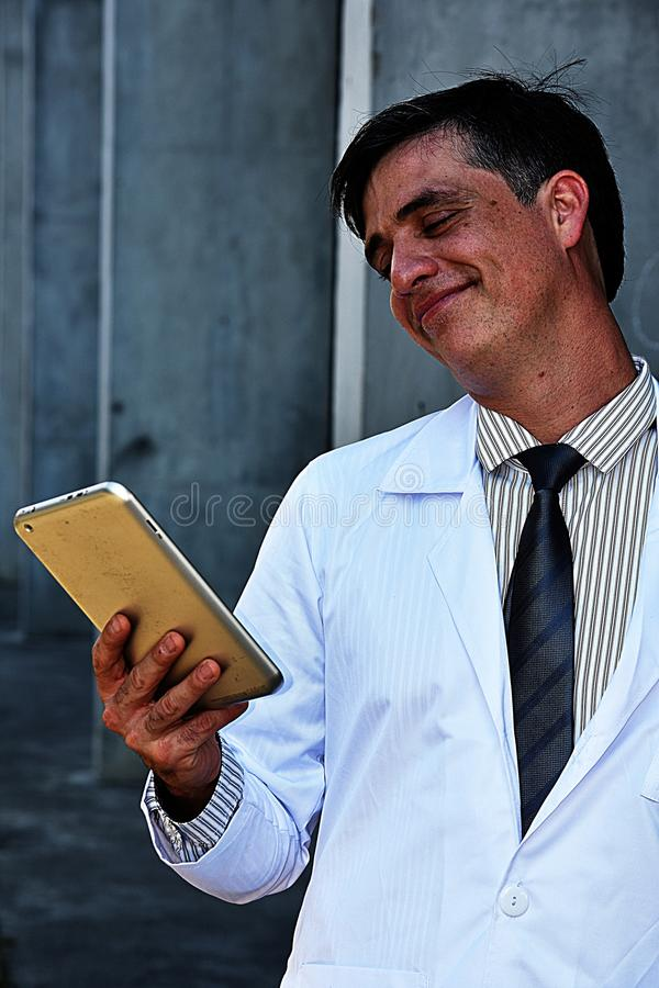 Happy Male Medic With Tablet. A handsome adult hispanic man stock images