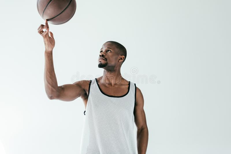 Handsome african american basketball player spinning ball on finger. Isolated on white royalty free stock photography