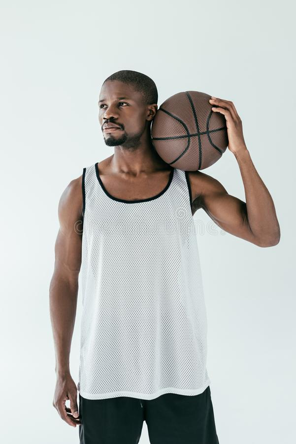 Handsome african american basketball player in sportswear with ball. Isolated on white royalty free stock images