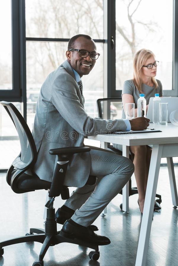 Handsome african american businessman in eyeglasses smiling at camera while working with female colleague. In office royalty free stock images