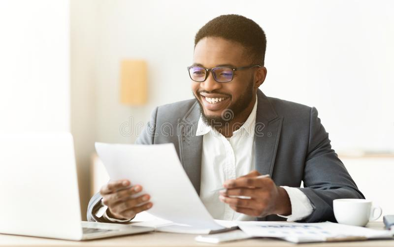 Handsome african american entrepreneur working with documents in office. Handsome african american entrepreneur working with financial documents in office, copy royalty free stock photos