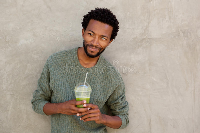 Handsome african american man holding fruit juice drink royalty free stock photography