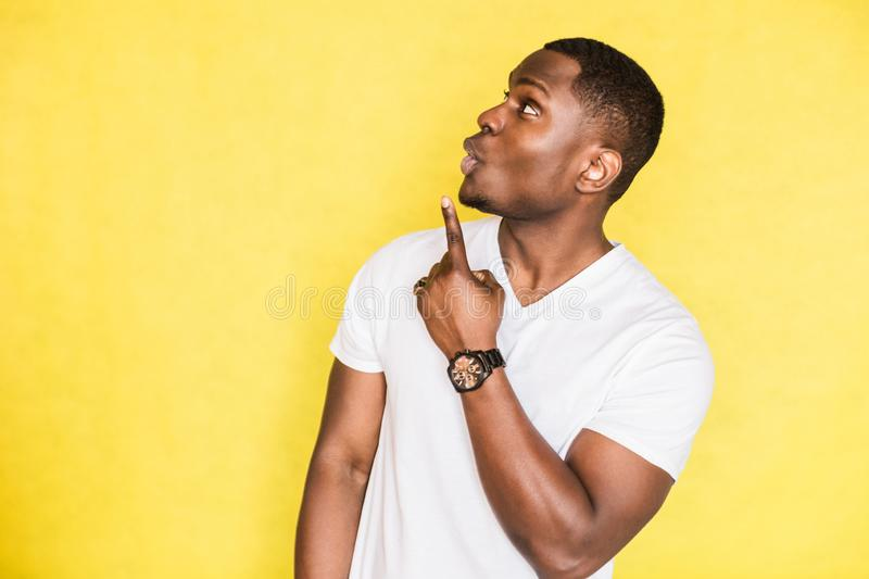 Handsome African American man indicates with forefinger at blank copy space. royalty free stock image