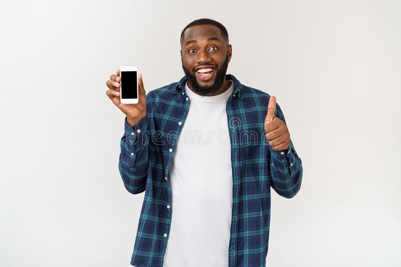 Handsome african american man isolated on grey background, presenting smart phone. Handsome african american man isolated on grey background, presenting smart stock photography