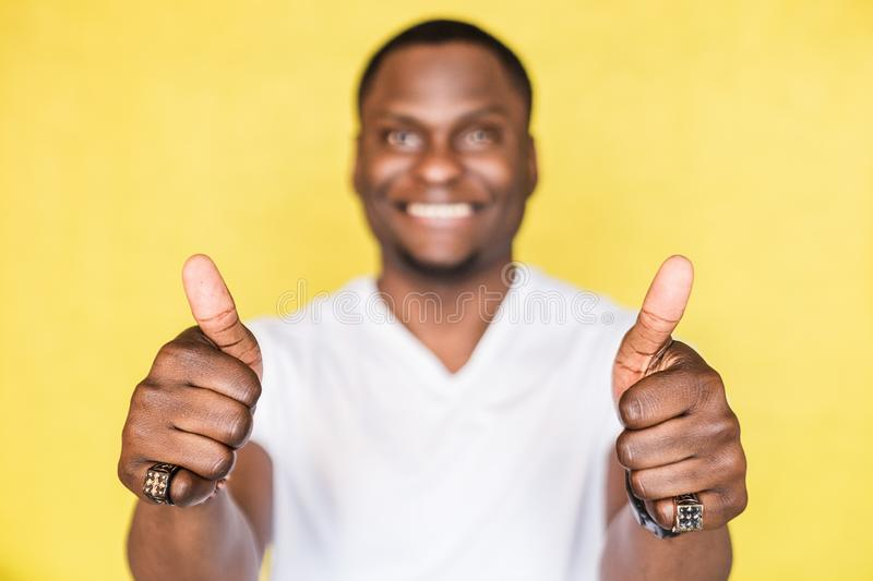 Handsome African American man shows thumbs up sign. Body language concept. stock images