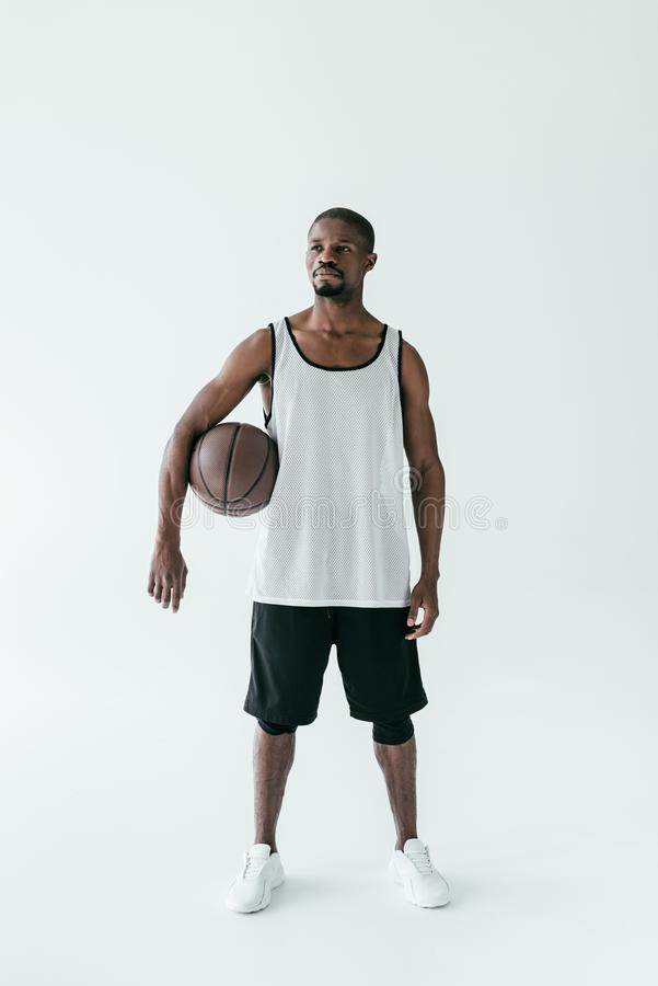 Handsome african american man in sportswear with basketball ball. Isolated on white royalty free stock image