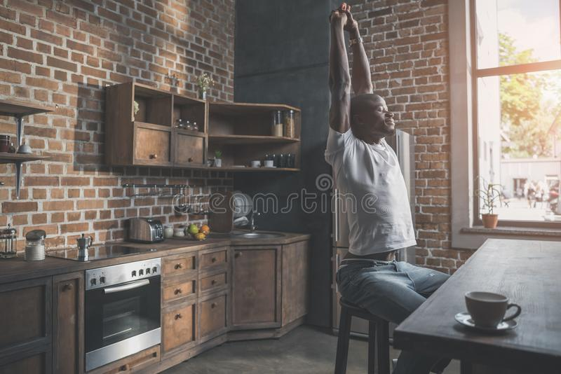 Handsome african american man stretching with pleasant smile while sitting stock photo